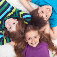 bigstock-Three-kids-laying-on-the-floor-33820607FI